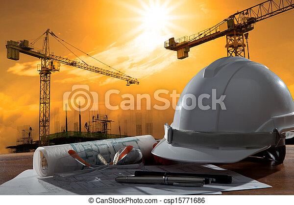 Die Akte mit Sicherheitshelm und Architekt auf Holztisch mit Sonnenuntergang und Baubau - csp15771686