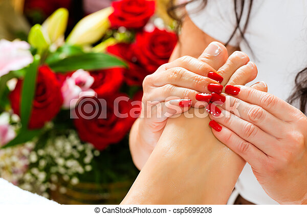 Eine Frau im Nagelstudio bekommt Fußmassage. - csp5699208