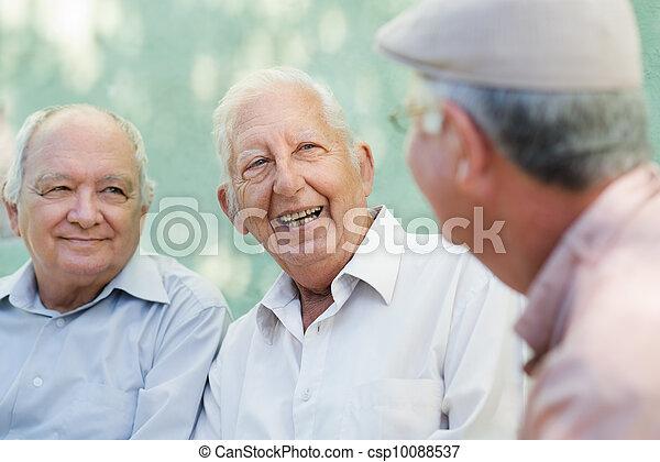 Eine Gruppe glücklicher älterer Männer lacht und redet - csp10088537