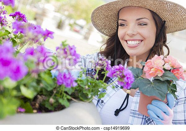 Eine junge erwachsene Frau, die einen Hut im Garten trägt - csp14919699
