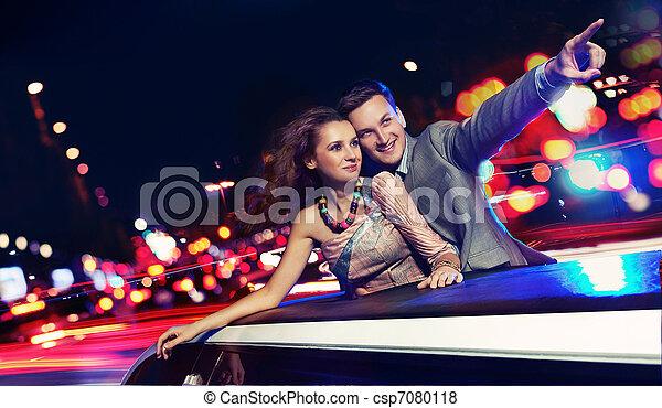 Elegantes Paar fährt nachts eine Limousine - csp7080118