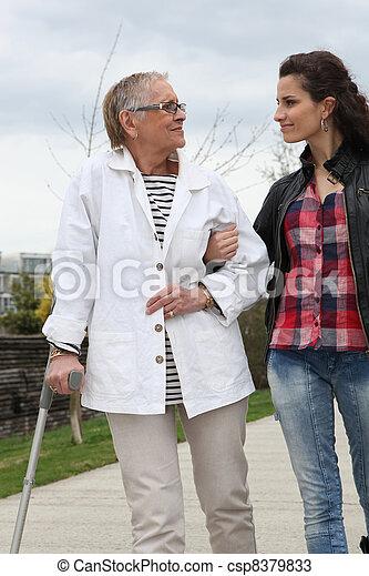 Eine junge frau, die älteren menschen hilft, mit einer