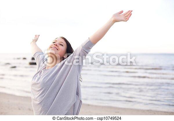 Glückliche Frau, die ihre Arme streckt, um die Natur zu genießen - csp10749524
