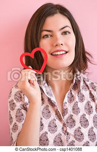 Glückliches Mädchen, das ein Herz hält. - csp1401088