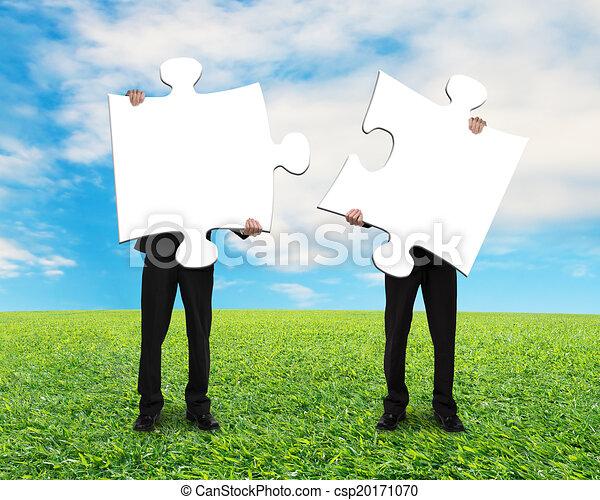 Zwei Männer mit leeren Puzzles auf Grasboden - csp20171070