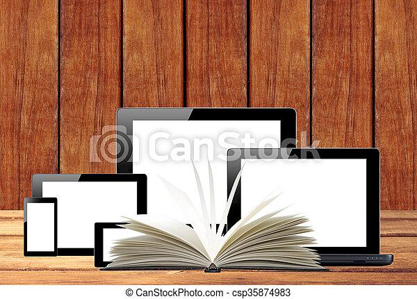 Tablet PC, Handy, Computer und offenes Buch auf Holztisch - csp35874983