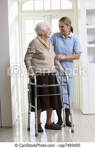 Pfleger, der älteren Frau beim Laufen hilft - csp7493400