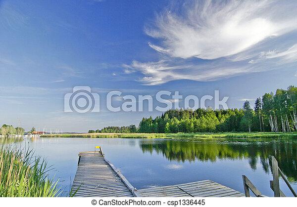 Ruhiger See unter lebendigem Himmel im Sommer - csp1336445