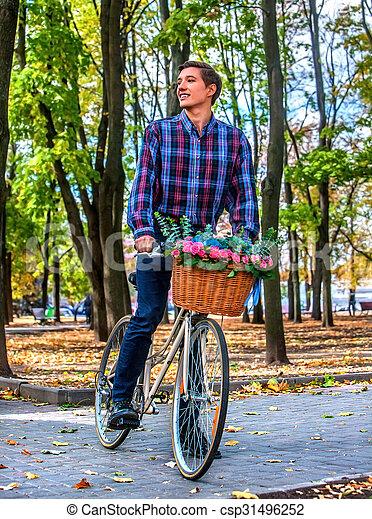 Schöne junge Frau mit Fahrrad im Park. - csp31496252