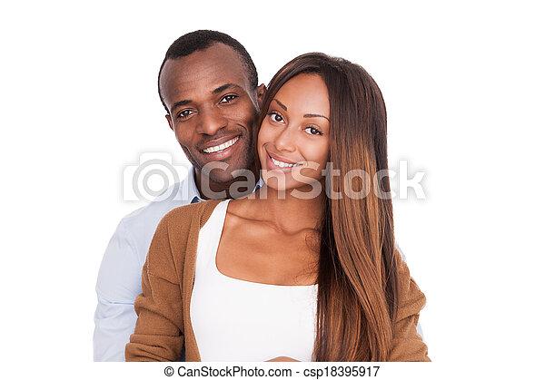 Schön, zusammen zu sein. Wunderschönes junges Afrikanisches Paar, das sich nahe steht und sich vor der Kamera lächelt, während es auf weiß isoliert ist - csp18395917
