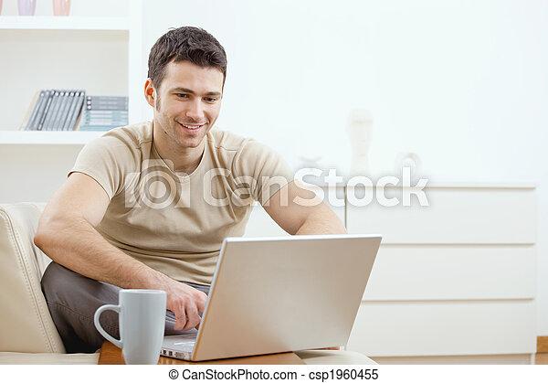 Ein glücklicher Mann, der Computer benutzt - csp1960455