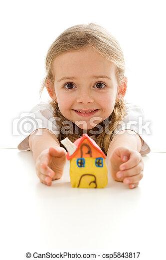 Ekstatisches kleines Mädchen mit ihrem Lehmhaus - csp5843817