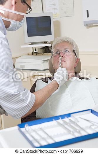 Zahnarzt im Untersuchungsraum mit Frau im Stuhl - csp1706929